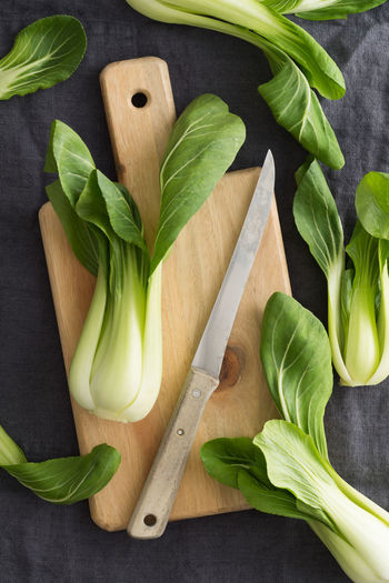 Cutting fresh pak choi with knife and cutting board on linen Green Knife Bok Choi Directly Above Food Pak Choi Pak Choio Pak Choy Vegetable