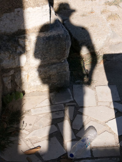 Albania Albania Tour Cowboy Hat Plastic Bottle Wall Aa Butrint Day Focus On Shadow Garbage High Angle View Lifestyles Litter Outdoors People Real People Shadow Standing Stone Sunlight Western