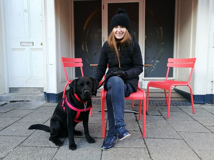 Portrait of smiling mature woman by dog sitting on chair at sidewalk