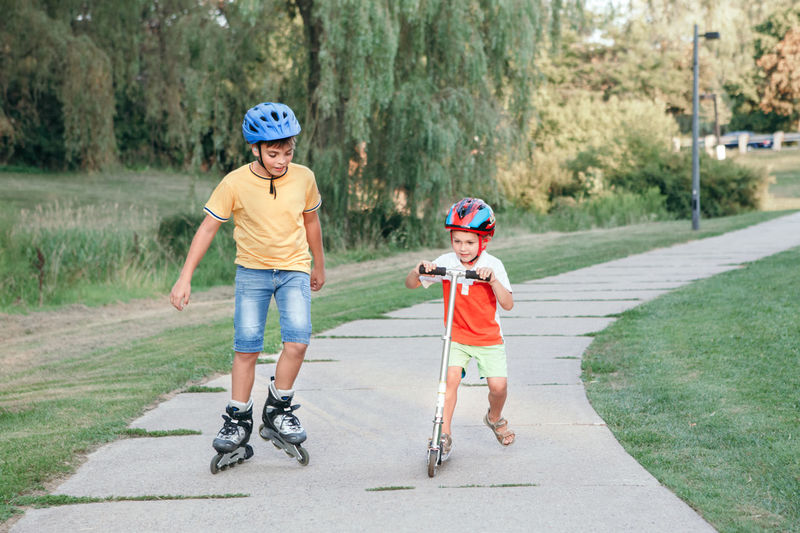 Boy skating while brother riding push scooters on footpath in park