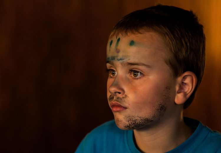 Close-up of boy with face paint looking away