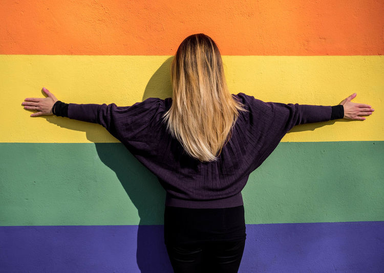 Rear view of woman with arms outstretched standing against colorful wall