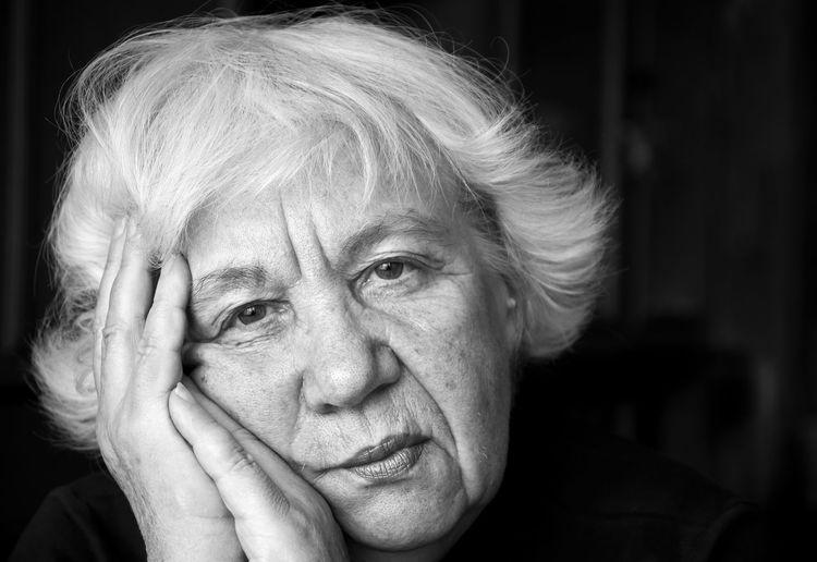 Portrait of sad senior woman against black background