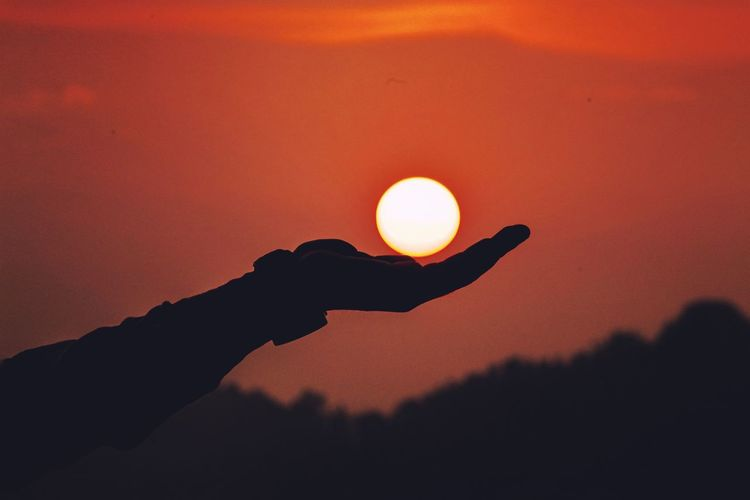 Optical illusion of silhouette hand holding sun during sunset
