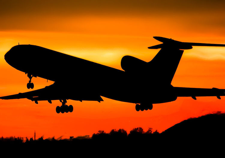Sunset Silhouette Sky Air Vehicle Orange Color Airplane Nature Mode Of Transportation Transportation on the move No People Flying Beauty In Nature Outdoors Cloud - Sky Travel Scenics - Nature Mid-air Low Angle View Mountain Aerospace Industry