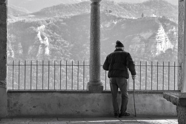 Rear view of man standing by railing against mountain
