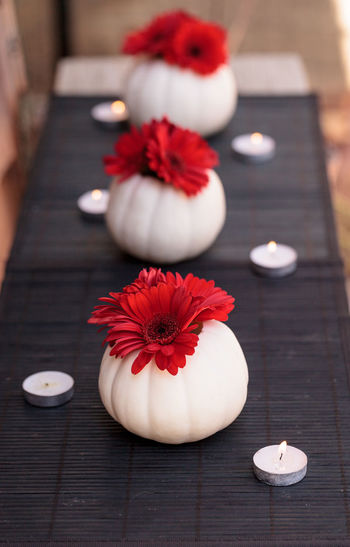 Close-up of red flowers in vases and tealight candles