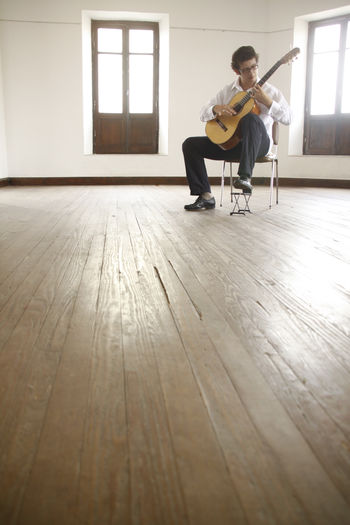 Full length of man playing guitar while sitting on chair