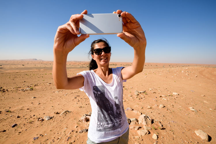 Woman taking self-portrait in the desert. Desert Nature Casual Clothing Communication Environment Fashion Front View Glasses Holding Land Leisure Activity Lifestyles Nature One Person Outdoors Photography Themes Portrait Real People Scenics - Nature Selfie Sky Sunglasses Wireless Technology Young Adult Young Women