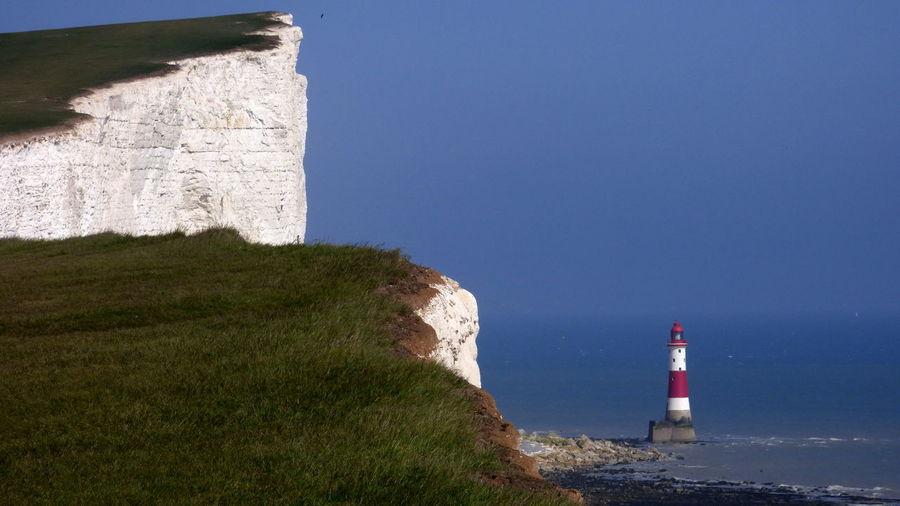Cliff against beachy head lighthouse in sea