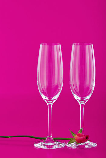 Close-up of wineglass on table against pink background