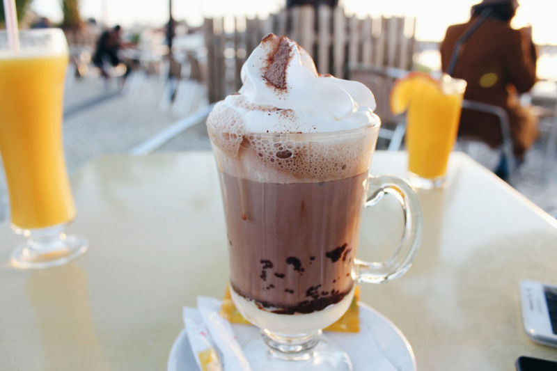 Close-up of coffee with whipped cream served on table at outdoor cafe