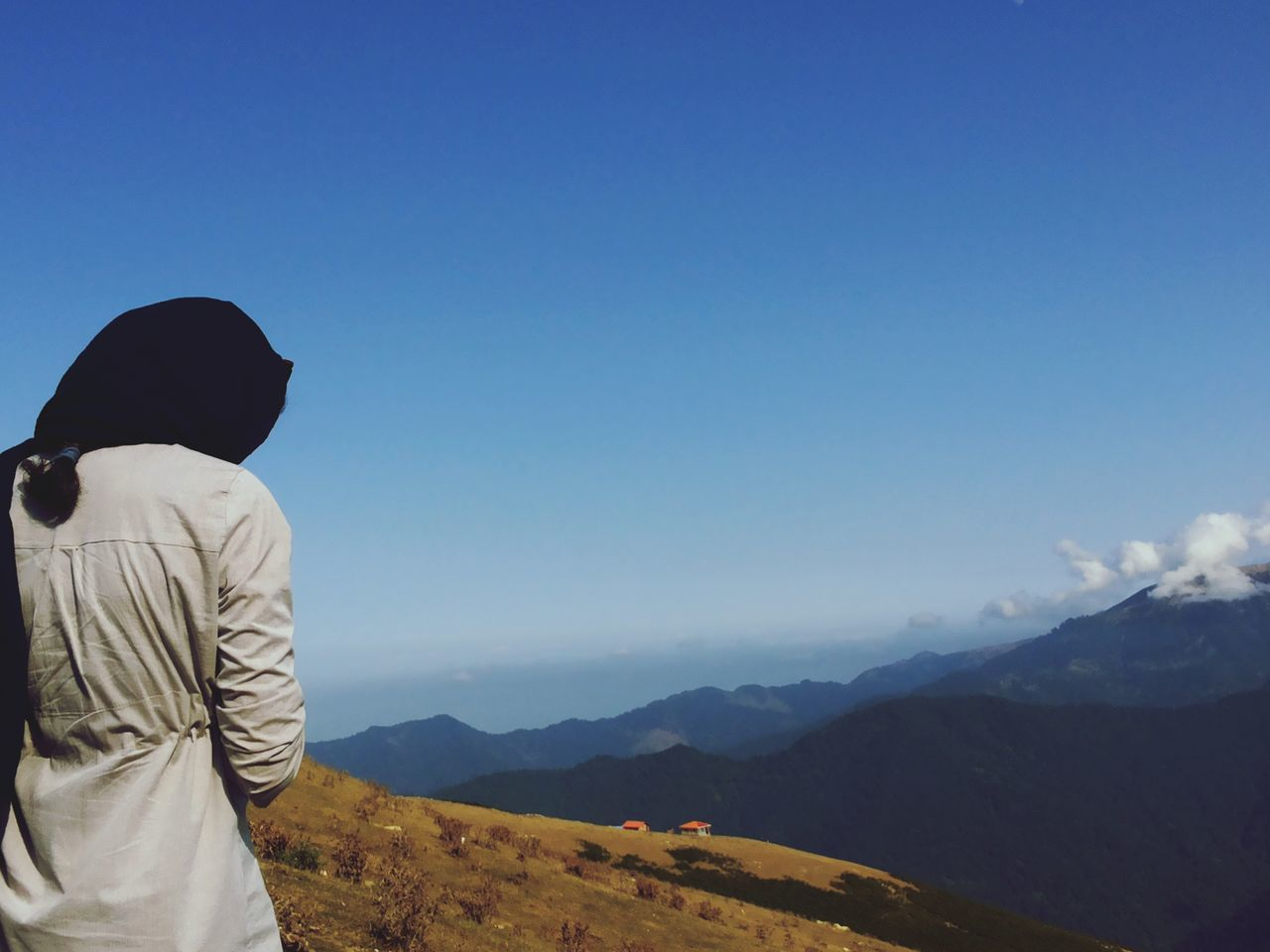 mountain, sky, real people, leisure activity, rear view, one person, lifestyles, beauty in nature, scenics - nature, tranquil scene, mountain range, non-urban scene, nature, tranquility, copy space, men, blue, environment, day, outdoors, looking at view, hood - clothing