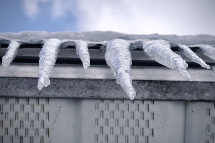 Close-up of icicles on roof against sky