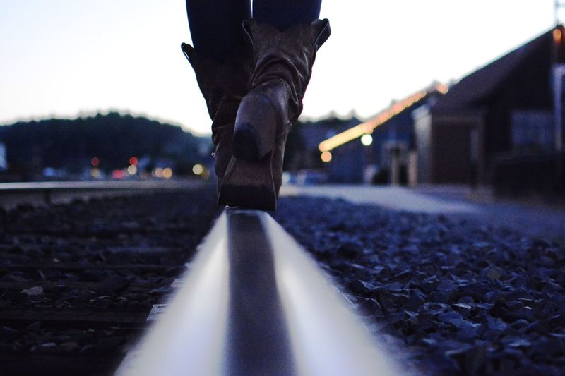 Low section of person walking on railroad track at dusk