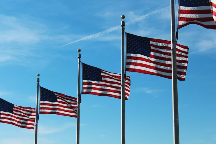 Low angle view of american flags fluttering against blue sky