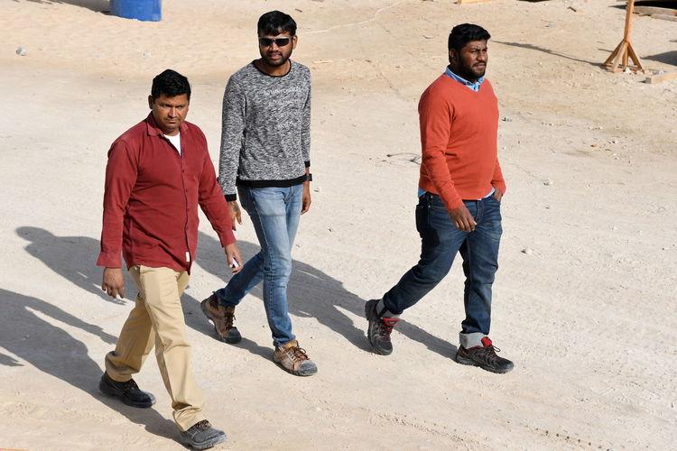 Full length of men walking on road