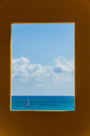 Sailboat on the ocean through a window Beauty In Nature Blue Boat Cloud - Sky Day Horizon Over Water Nature Nautical Vessel No People Ocean Outdoors Sailboat Scenics Sea Sky Tranquil Scene Tranquility Water