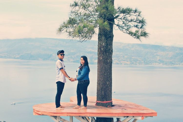 Full length of couple holding hands standing on heart shape by tree against sky