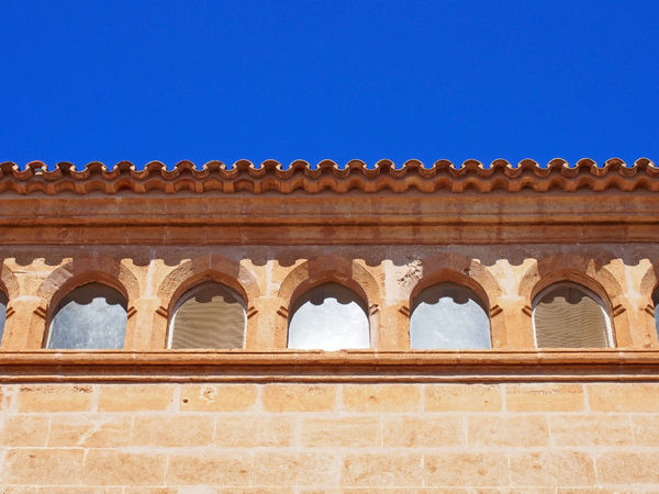close up of the roof line of an old stone spanish building with curved tiles and ornate windows with a bright blue sunlit sky Built Structure Architecture Building Exterior The Past History Low Angle View Day No People Sky Building Clear Sky Travel Destinations Blue Nature Art And Craft Copy Space Ancient Wall Craft Architectural Feature Outdoors Roof Tile Tiles