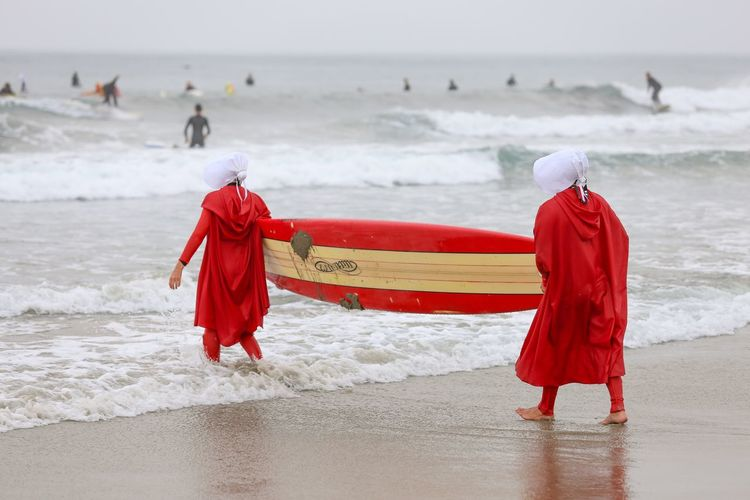 """Blackies Halloween Surf Contest Series • """"It's their own fault. They should have never given us uniforms if they didn't want us to be an army"""" of surfers.-Handmaid's Tale Red Beach Walking Sea Full Length Wave Nature Carrying Water Beauty In Nature Standing Day Sand Lifestyles Horizon Over Water Outdoors Women Halloween 2017 Handmaid's Tale Costume Surfers Surf Surfing Surfboard Halloween Costumes California Dreamin"""
