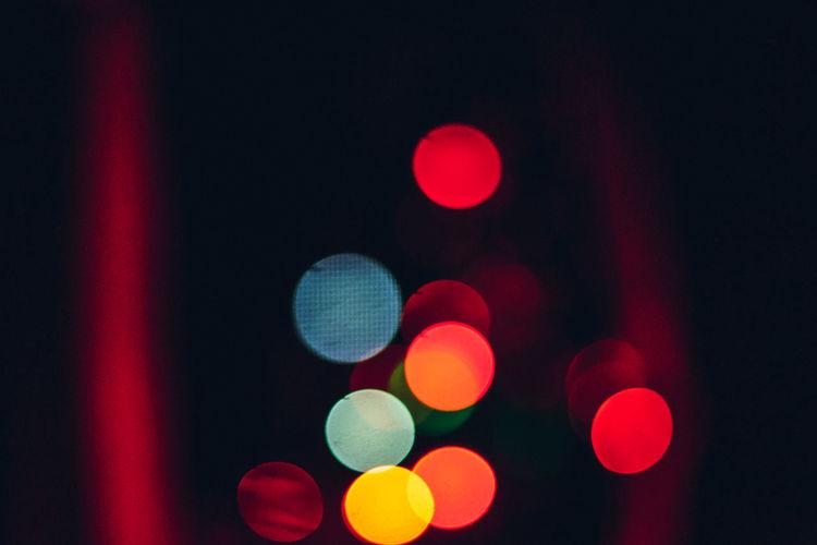 Defocused image of illuminated lights on street at night
