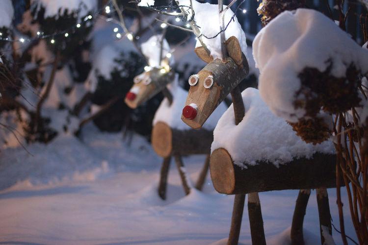 Wooden reindeer sculptures on snow covered field