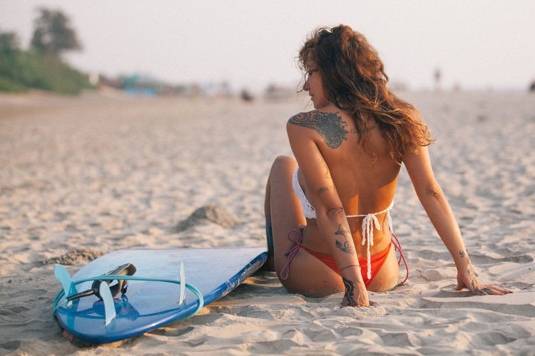 Rear view of mid adult woman by surfboard relaxing at sandy beach