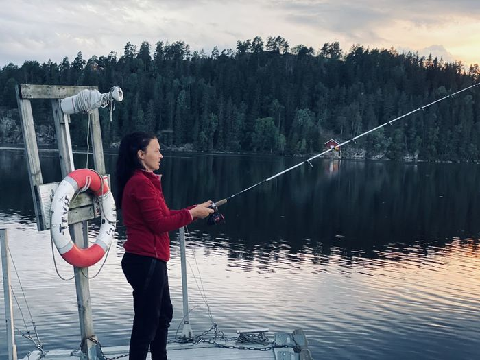 Full length of woman fishing on lake against sky