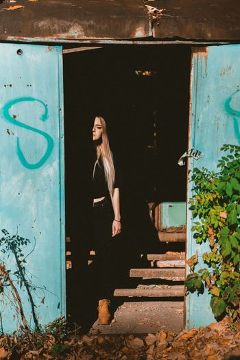 Full length of woman standing at entrance of abandoned building