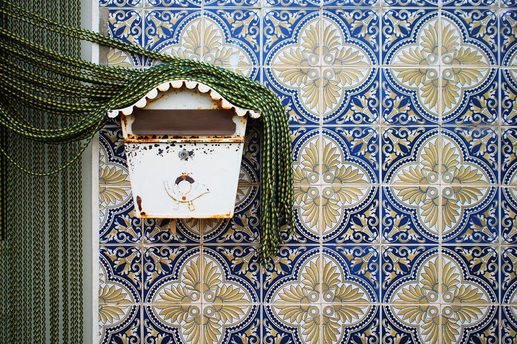 Beaded curtain on rusty mailbox over wall