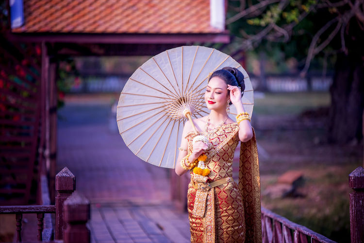 Beautiful woman in traditional clothing holding paper umbrella while standing on footbridge