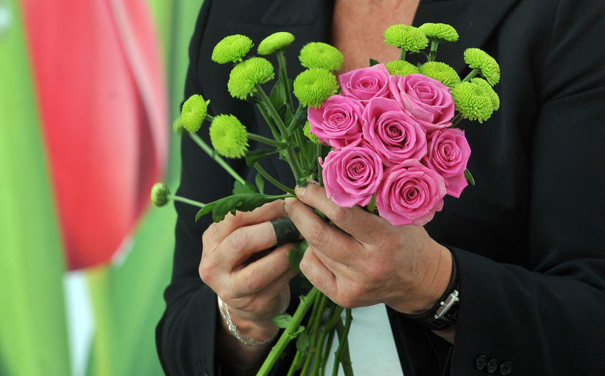 Midsection Of Florist Holding Flowers