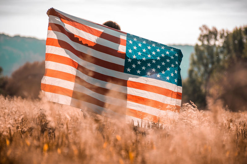 Girl holding American flag in crop field. Sunny Vibes America Crowd Day Emotion Field Flag Girl Girls Land Model Nature Outdoors Patriotism Plant Posing Pride Selective Focus Shape Sky Star Shape Striped Summer Vibes Tree First Eyeem Photo My Best Travel Photo