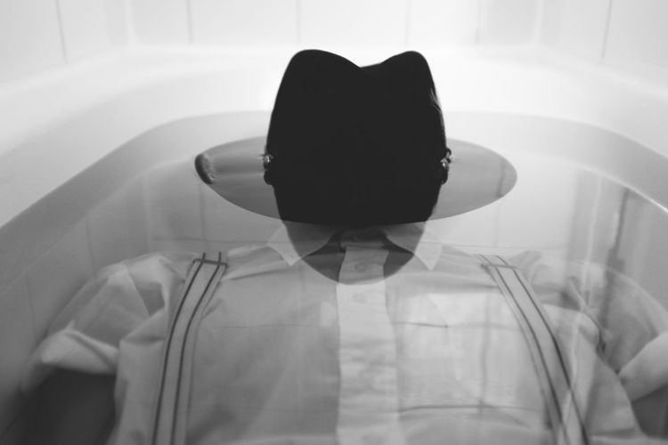 Rear view of man wearing hat at home