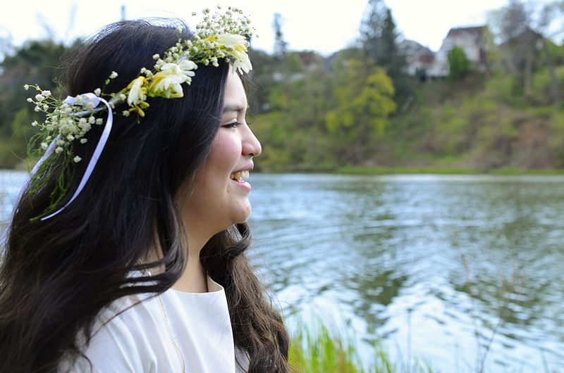 Side view of happy young woman wearing flower wreath by river