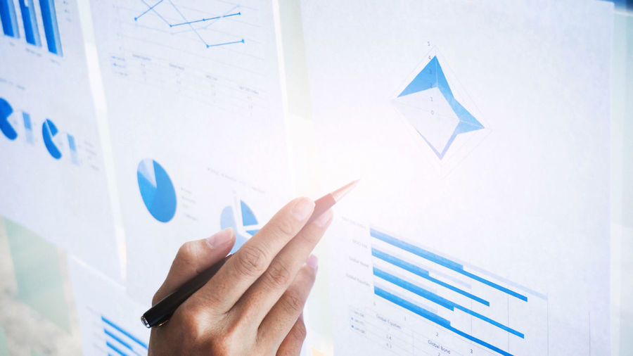 High angle view of businessman pointing using pen at graphs on window