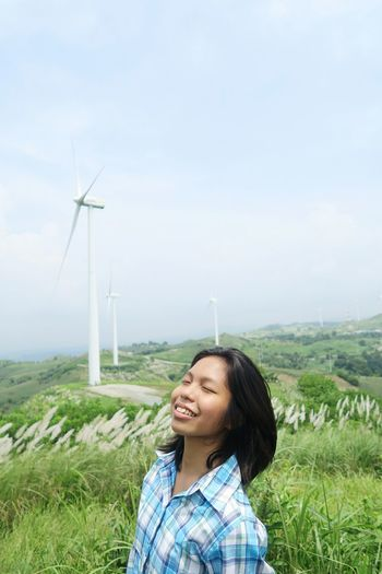 Smiling woman standing on land against windmills and sky