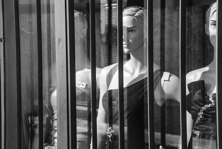 Clothing on mannequin seen through glass window of store