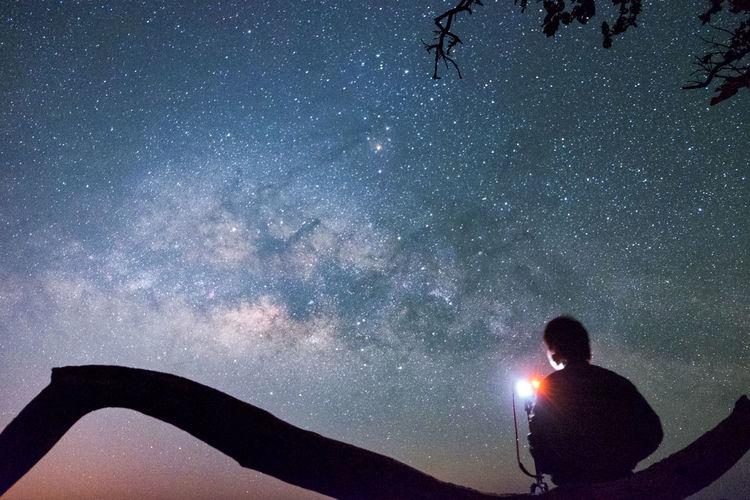 Silhouette man with illuminated lighting equipment against star field