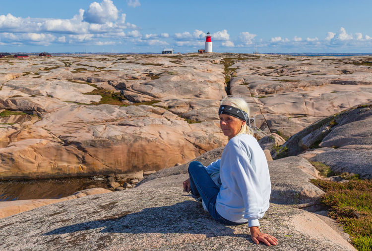 Woman Sitting On Rock In Sunny Day