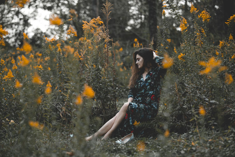 Woman Sitting Amidst Plants In Forest