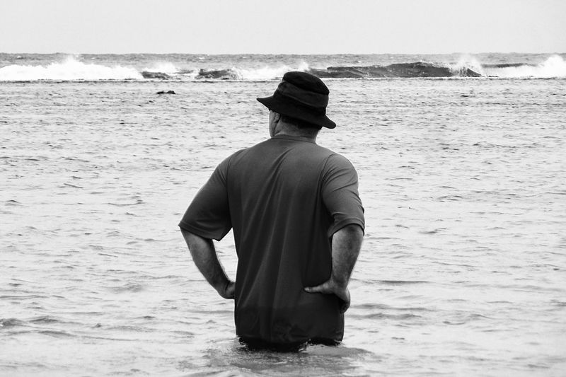 Rear view of man with hands on hip standing in sea