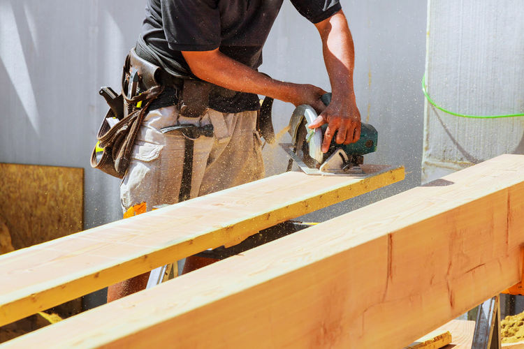 Midsection of man cutting plank during sunny day