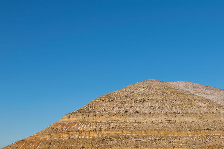 Low angle view of historical egyptian pyramid against blue sky