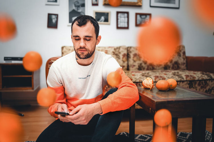 One Person Indoors  Front View Lifestyles Real People Home Interior Casual Clothing Men Males  Orange Color Adult Young Adult Healthy Lifestyle Focus On Foreground Food And Drink Young Men Table Food