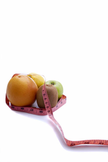 Healthy food isolated Apple Diet Food And Drink Close-up Concept Copy Space Die Fitness Food Freshness Fruit Fruits Healthy Eating Lifestyles Measure Meter No People Orange Color Still Life Studio Shot Tape Weightloss Weights White White Background