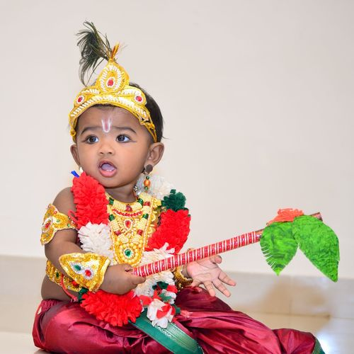 Cute girl in krishna costume playing at home