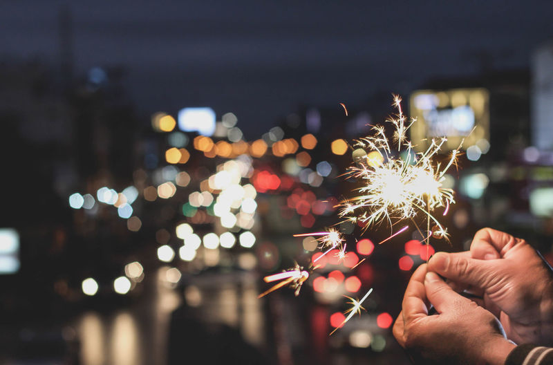 Cropped hands of person holding illuminated sparkler at night