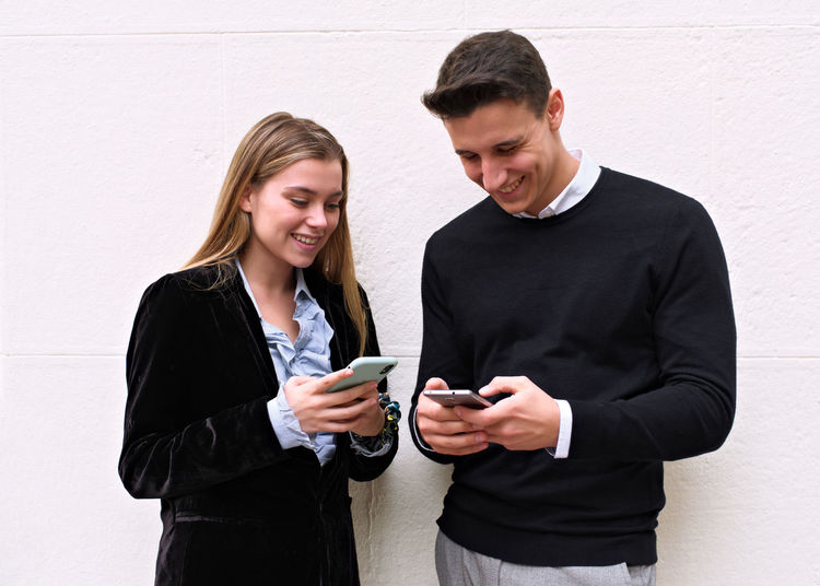 Smiling young woman using phone while standing against wall